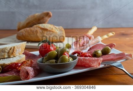 Antipasto Platter A Cold Meat Plate With Prosciutto, Slice Of Ham,salami, Decorated With Olives,drie