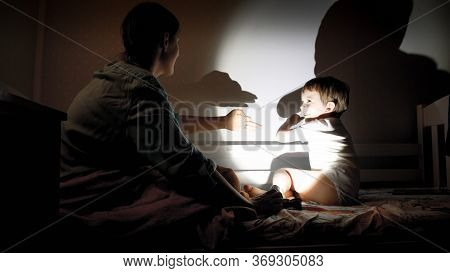Happy Smiling Little Boy And Young Mother Playing With Torch And Shadows From Their Hands On Wall At