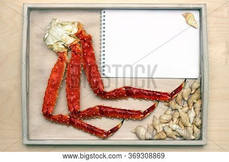 Legs Of A Boiled Crab On A Wooden Tray . White Sheet Of Notepad For Menu Or Order. Copy Space.