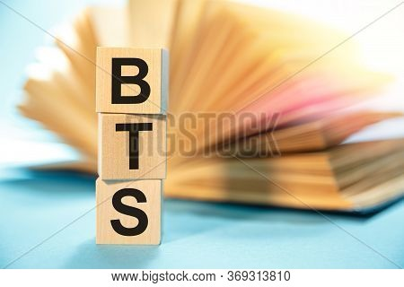 Bts Concept With Wooden Cubes. The Word Bts On The Background Of An Expanded Book