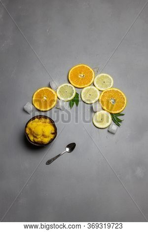 Coconut Bowl Full Of Citrus Fruit Sorbet Ice Cream And Small Metallic Spoon, Sliced Oranges And Lemo