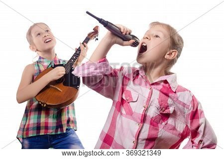 Two Cute Little Girls Posing With A Microphone And Domra. Concept Of Musician And Vocalist. Studio P