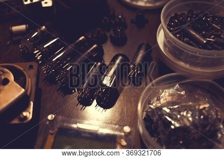 Electronic Vacuum Tubes And Other Electronic Components On The Table. Toned Background For Design.