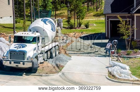 New Hill, North Carolina, USA; 6/1/2020: Concrete driveway being poured and set as part of a new house development.