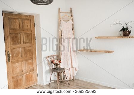 Wedding Interior. Charges The Bride At The Hotel. Wedding Photography. The Brides Dress Hangs Near T