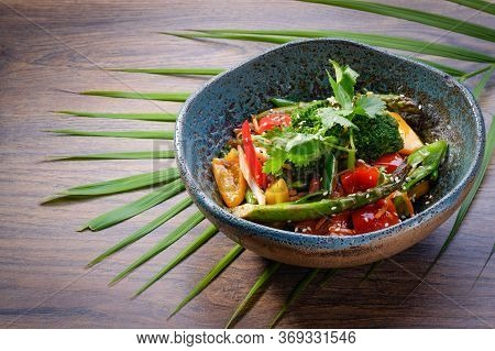 Wok Vegetables In A Bowl On Wooden Table Background. Traditional Asian Wok Side Dish. Broccoli, Aspa