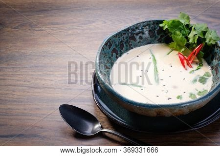 Tom Kha Soup Bowl On Wooden Table Background. Traditional Thai Asian Spicy Coconut Milk Soup. Tom Kh