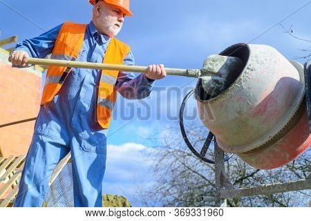 Builder Works With Concrete Mixer. Construction Worker With Spade In Hand. Concrete Mixer Prepares C