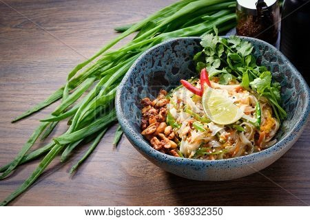 Pad Thai Noodles In A Bowl On Wooden Table Background. Thai Stir Fried Rice Noodles With Vegetables,
