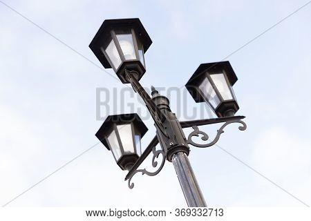 Classic Triple Streetlight With Glass Lamps. City Lightening.