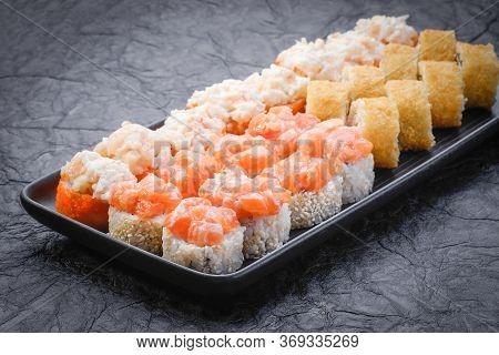 Sushi Set Served On Black Plate On Dark Background. Baked Maki Roll, Philadelphia Maki, Tempura Maki