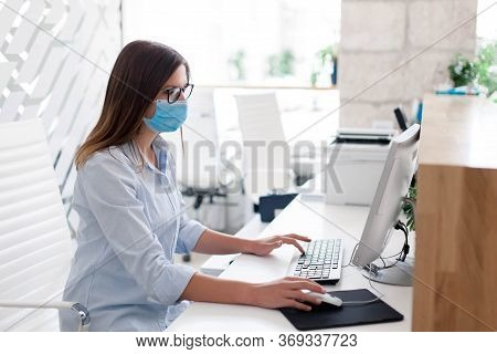 Young Woman Wearing Medical Mask In Office. Protection Employees On Workplace. Girl Working At Recep