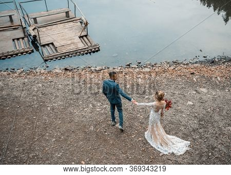 Beautiful Wedding Couple Bride And Groom At Wedding Ceremony On The Beautiful Lake Background. Happy