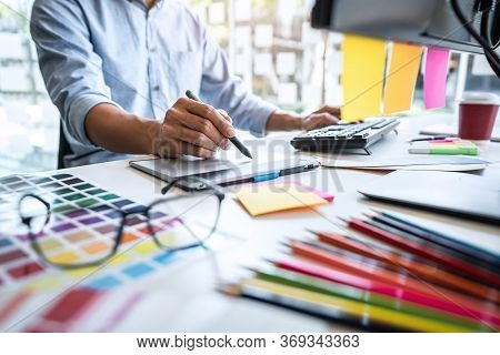 Two Colleague Creative Graphic Designer Working On Color Selection And Color Swatches, Drawing On Gr