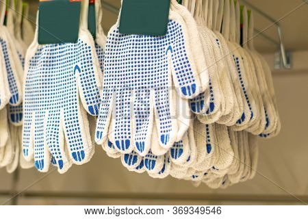 White Fabric Gloves With A Blue Protective Layer. Garden Gloves In The Hardware Store. Gloves For Co