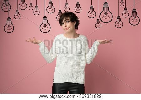 Beautiful young woman with nothing to do gesture over cartoon drawn lamps. Girl using language of body to say apologies, regret, failure, no idea bulbs above head. Creative crisis, difficult problem