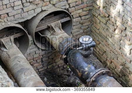 An Open Underground Pipeline With Valves In A Brick Well. Underground Communications Of Water Supply