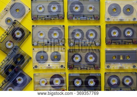 Vintage Audio Cassettes On A Yellow Background. 90s Music On Audio Cassettes. Many Audio Tapes With