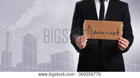Bankrupt Enterprise. Business Person Holds A Cardboard Tablet With The Word Bankrupt On The Backgrou