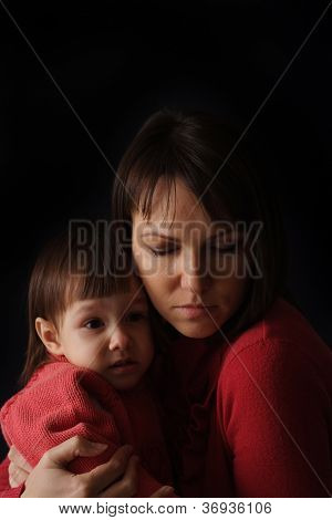 A pretty Caucasian mother with a sad crying daughter