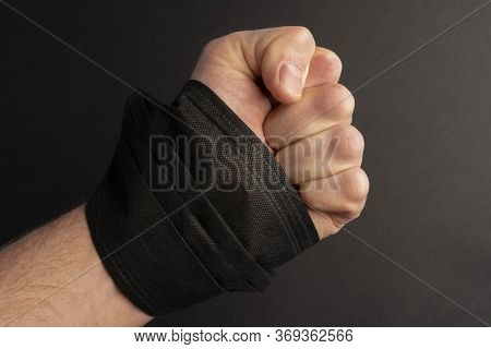 Fist With A Black Mask In His Hand On A Black Background. A Symbol Of Protest And Unrest In The Unit