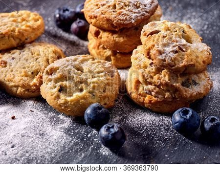 Bakers gonna bake. Serving food on slate. Oatmeal cookies biscuit with blueberry on dark tiles countrylike. Chocolate chip cookies shop on window display. Lunch in inexpensive cafe.