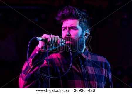 Man With Enthusiastic Face Holds Microphone, Singing Song, Black Background.