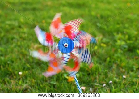 Children's Colorful Plastic Toy Windmill  Turbine On Green Blurred Grass Background Outdoors In Sunn