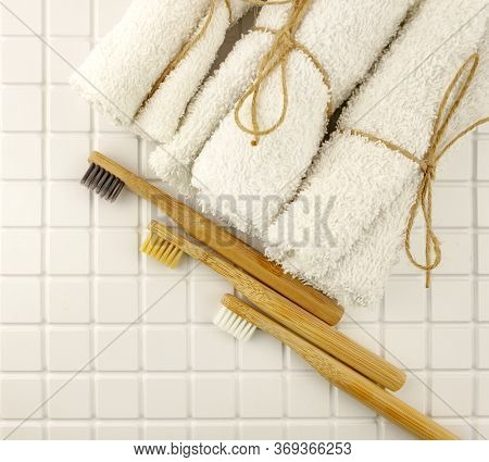 Family Set Of Tree Wooden Bamboo Toothbrushes With White Towels On White Tile Bathroom Background. E