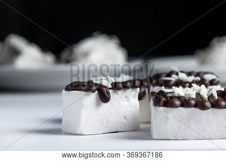 White Marshmallow Poured By Dark Chocolate. Marshmallows On A Black Background. Sweet Cuisine