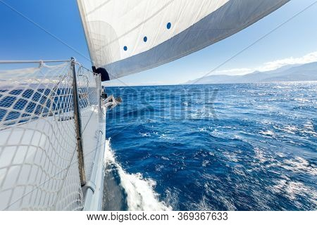 Sail boat, Sailing with fresh speed wind. A view from the yacht's deck to the bow and sails. Sail boat with set up sails gliding in open sea. Greece, Europe