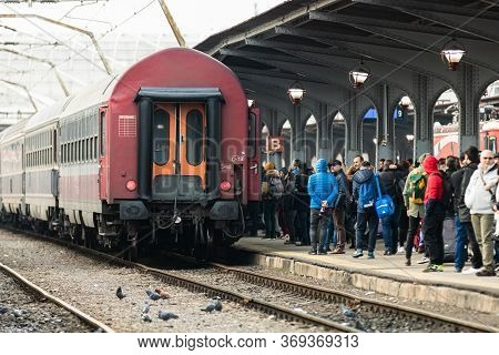 Travelers And Commuters Waiting For A Train On The Train Platform Of Bucharest North Railway Station
