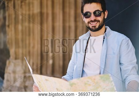 Positive Hipster Guy In Casual Wear Resting On Old Stairs During Sightseeing Tour In City