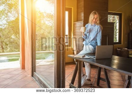 Working from home. Woman with laptop and drinking tea, spend free time on terrace. Staying connected, Social distancing, internet, chatting. Work life, new reality.