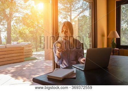 Working from home. Woman talking on video call with Family, using smartphone and drinking tea. Online chat. Spend free time on terrace. Staying connected, Social distancing, internet, chatting.