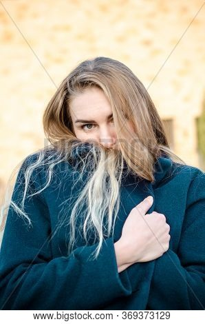 Portrait Of A Beautiful Young Blonde Girl In A Blue Coat, Who Froze And Hides In Her Collar, At Suns