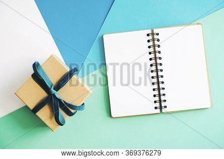 An Open Notebook And Gift Box. Gift Craft Box And Notepad With A Clean White Page. Gift Craft Box Ti