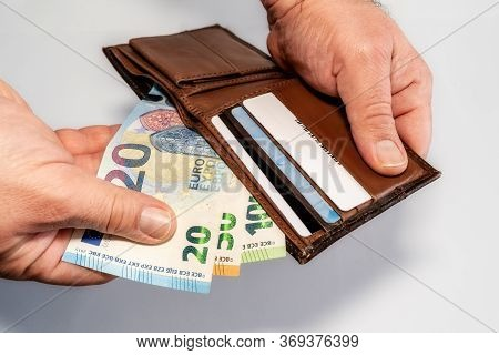 Mans Hand Holding A Brown Wallet With 20, 50 And 100 Euro Money, Isolated On White Background. High