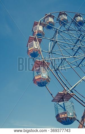 A Low Angle View Of A Vintage Ferris Wheel Fairground Ride With Enclose Seating Under A Blue Sky And