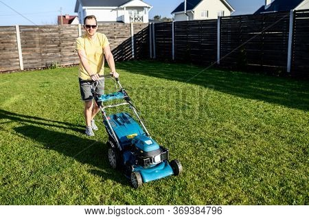 A Young Guy Mows A Lawn With A Lawn Mower. Backyard Gardening