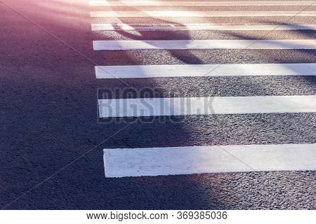 Pedestrian Crossing Shadows Of People On A Zebra Safety