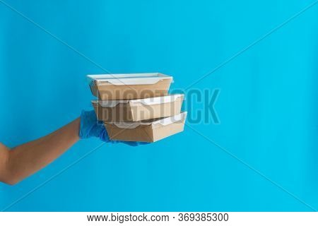 Courier Delivery Of Food In Containers. Courier Girl Holding Containers On A Blue Background. Delive