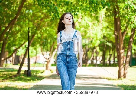 Portrait of a young beautiful teenager girl in blue jeans overalls walking in summer park