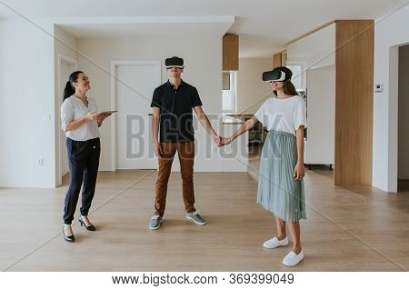 Estate Agent In Her 40s Discussing With Young First Time Buyers In Modern Apartment.