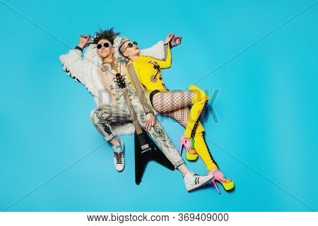 A portrait of two cool young punk people posing in the studio. Casual punk fashion, rock band.