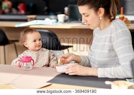 family, eating and people concept - happy mother with puree and spoon feeding little baby girl sitting in highchair at home