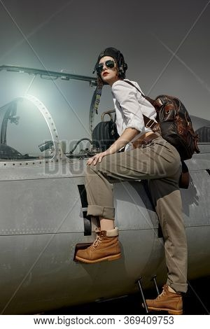 Portrait of a beautiful girl pilot wearing helmet and sunglasses sits in her fighter jet at the airfield. Military aircraft.