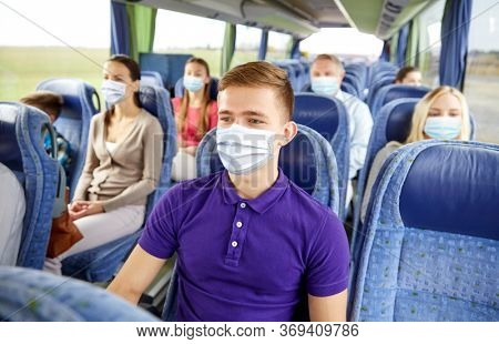 transport, tourism, road trip and people concept - young man wearing face protective medical mask for protection from virus disease sitting in travel bus or train