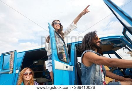 summer holidays, road trip, travel and people concept - smiling happy young hippie friends in minivan car at seaside