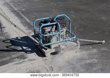 A Power Cement Machine Blade And Machine Cut An Expansion Line On A Freshly Poured Concrete Floor.